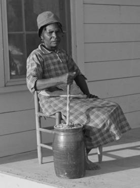 Gertrude Miller churning butter on the porch